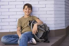 Bambino allegro che porta il suo zaino Immagini Stock Libere da Diritti
