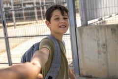 Bambino allegro che porta il suo zaino che sta davanti allo Sc Immagini Stock Libere da Diritti