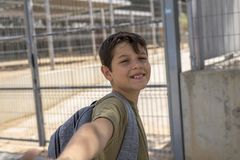 Bambino allegro che porta il suo zaino che sta davanti allo Sc Immagine Stock