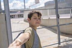 Bambino allegro che porta il suo zaino che sta davanti allo Sc Immagine Stock Libera da Diritti