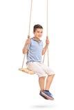 Bambino allegro che si siede su un'oscillazione Fotografie Stock