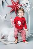 Bambino allegro che si siede su una slitta di natale fotografie stock