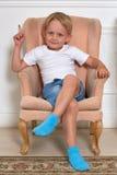 Bambino allegro che si siede sulla poltrona Fotografie Stock