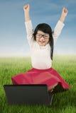 Bambino allegro con il computer portatile sull'erba Immagine Stock