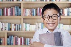 Bambino allegro con il libro che sorride nella biblioteca Immagini Stock