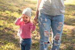 Bambino allegro con la madre che cammina insieme a tenersi per mano nel parco di estate su erba L'oggetto principale è bambino Mo immagine stock