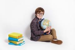 Bambino allegro in modo divertente con il globo che si siede su un pavimento Istruzione Immagine Stock Libera da Diritti