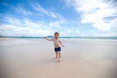 Bambino allegro su una spiaggia tropicale Immagini Stock