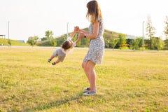 Bambino allegro sveglio con il gioco della madre all'aperto in parco fotografie stock libere da diritti