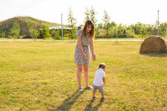 Bambino allegro sveglio con il gioco della madre all'aperto in parco immagini stock libere da diritti