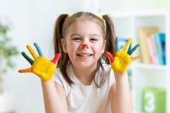 Bambino allegro sveglio con le mani ed il viso dipinti Immagini Stock Libere da Diritti