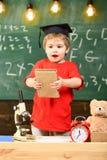 Bambino, allievo sul fronte allegro vicino al microscopio Il ragazzo del bambino in cappuccio laureato tiene il libro in aula, la Fotografie Stock