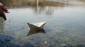 Bambino allo stagno con una barca di carta archivi video