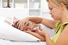 Bambino ammalato con alta febbre e una madre preoccupata Fotografia Stock