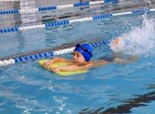 Bambino 7 anni di ragazzo che impara nuotare nello stagno di rivestimento. Fotografia Stock Libera da Diritti