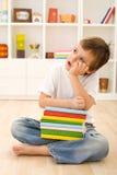 Bambino annoiato con i lotti dei libri di banco Immagini Stock Libere da Diritti