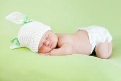 Bambino appena nato addormentato divertente. Protezione del coniglietto sulla sua testa fotografia stock libera da diritti