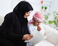 Bambino arabo felice a casa con sua madre Fotografie Stock