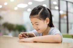 Bambino asiatico che esamina smartphone lo scrittorio delle biblioteche Fotografia Stock