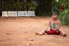 Bambino asiatico che gioca con la sabbia e la palla nel campo da giuoco Fotografia Stock