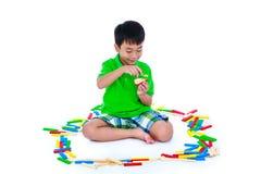 Bambino asiatico che gioca i blocchetti di legno del giocattolo, isolati su backgroun bianco Fotografia Stock