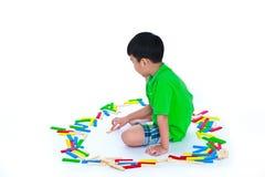 Bambino asiatico che gioca i blocchetti di legno del giocattolo, isolati su backgroun bianco Fotografia Stock Libera da Diritti