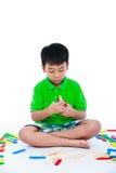 Bambino asiatico che gioca i blocchetti di legno del giocattolo, su backgroun bianco Fotografia Stock