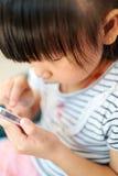 Bambino asiatico che gioca il telefono della mano fotografie stock libere da diritti
