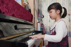 Bambino asiatico che gioca piano Fotografia Stock