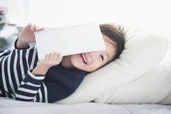 Bambino asiatico che legge un libro Fotografia Stock
