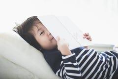 Bambino asiatico che legge un libro Fotografie Stock Libere da Diritti