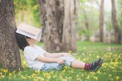 Bambino asiatico che legge un libro Immagine Stock