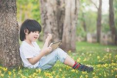 Bambino asiatico che legge un libro Immagini Stock