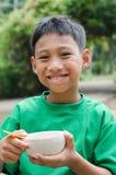 Bambino asiatico che mangia la prima colazione Fotografia Stock