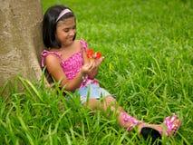 Bambino asiatico che osserva un fiore fotografia stock libera da diritti
