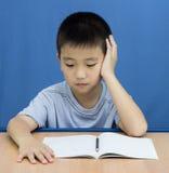 Bambino asiatico che pensa qualcosa scrivere immagine stock