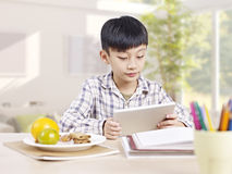 Bambino asiatico che per mezzo del computer della compressa Immagine Stock Libera da Diritti