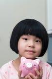 Bambino asiatico con il porcellino salvadanaio Fotografie Stock Libere da Diritti
