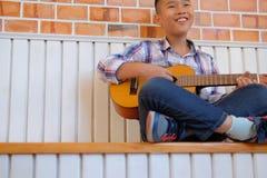 bambino asiatico del ragazzo del bambino che gioca le ukulele della chitarra atto di svago dei bambini immagine stock libera da diritti