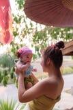 Bambino asiatico della tenuta della mamma a disposizione Immagine Stock