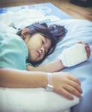 Bambino asiatico di malattia ammesso in ospedale con il gocciolamento salino del dispositivo di venipunzione sopra immagini stock