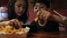 Bambino asiatico felice che guarda sul telefono cellulare e godere di di mangiare i fuochi della patata, movimento lento del frat stock footage