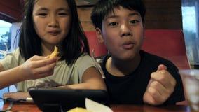 Bambino asiatico felice che guarda sul telefono cellulare e godere di di mangiare i fuochi della patata, movimento lento del frat video d archivio