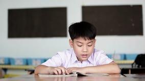 Bambino asiatico nella lettura e nella scrittura dell'uniforme dello studente per fare compito della scuola video d archivio