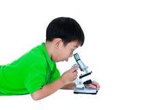 Bambino asiatico osservato attraverso una preparazione biologica del microscopio Fotografia Stock