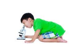 Bambino asiatico osservato attraverso una preparazione biologica del microscopio Fotografia Stock Libera da Diritti