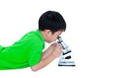 Bambino asiatico osservato attraverso una preparazione biologica del microscopio Fotografie Stock