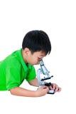 Bambino asiatico osservato attraverso una preparazione biologica del microscopio Immagine Stock