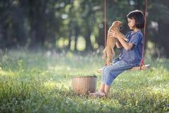 Bambino asiatico su oscillazione con il cucciolo Fotografia Stock Libera da Diritti