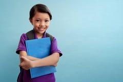 Bambino asiatico sveglio che tiene un libro Fotografia Stock Libera da Diritti